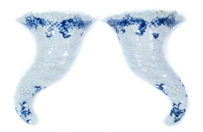 Lot 64 - Rare pair of Worcester cornucopia wall pockets, circa 1755, moulded with landscape scenes, with floral and other patterns in underglaze blue, painter's marks to backs, 21cm long