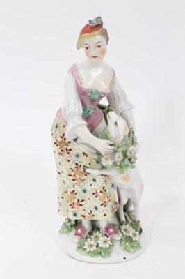 Lot 66 - Derby figure of a shepherdess, circa 1760-65, polychrome and gilt decorated, shown garlanding a lamb, standing on a floral encrusted base, patch marks to base, 19.5cm high