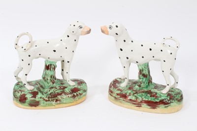 Lot 68 - Pair of Staffordshire pottery models of Dalmatians, shown standing on naturalistic bases, 16cm high