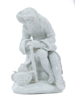 Lot 73 - Bow blanc de chine figure, circa 1755, in the form of a seated elderly man warming his hands on a brazier, emblematic of Winter, 12.5cm high
