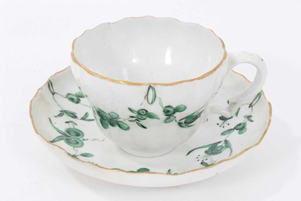 Lot 74 - Bristol cup and saucer, circa 1772-75, decorated in green enamels with swags of flowers, with gilt rims, B marks to bases, the saucer measuring 12cm diameter