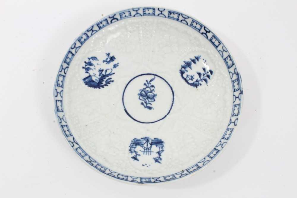 Lot 80 - Lowestoft blue and white saucer, circa 1765, relief moulded, with circular panels containing Chinese landscapes and a patterned border, 12.25cm diameter