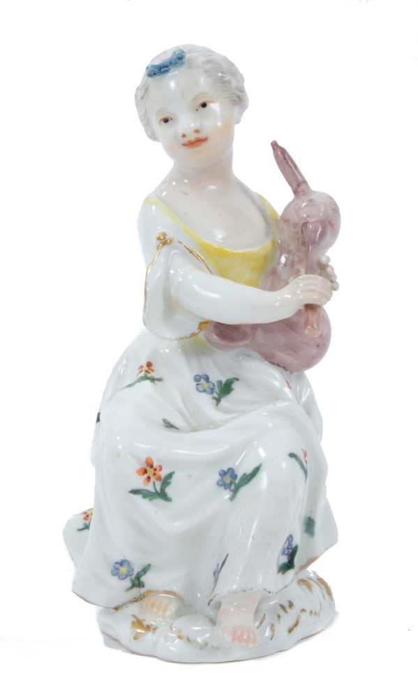 Lot 82 - Meissen figure of a young girl, circa 1755, shown seated on a tree stump playing pipes, decorated in enamels and gilt, incised number 23 to base, 12cm high