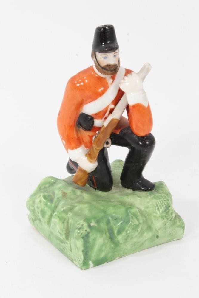 Lot 85 - Unusual Derby (King Street Works) figure of a kneeling soldier, circa 1890-1910, polychrome enamelled on a square naturalistic base, marks underneath, 10cm high