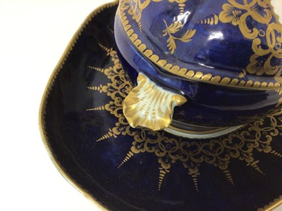 Lot 86 - Worcester oval sauce tureen, cover and stand, circa 1772-75, polychrome painted with flowers on a cobalt blue and gilt ground, the stand measuring 23cm across
