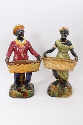 Lot 87 - Pair of continental majolica blackamoor figures, late 19th century, shown holding baskets and standing on grassy bases, 36cm and 38cm high